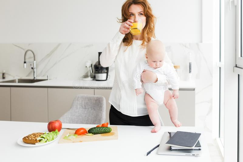 Beautiful woman holding her cute little baby while drinking juice and cooking on kitchen royalty free stock photography