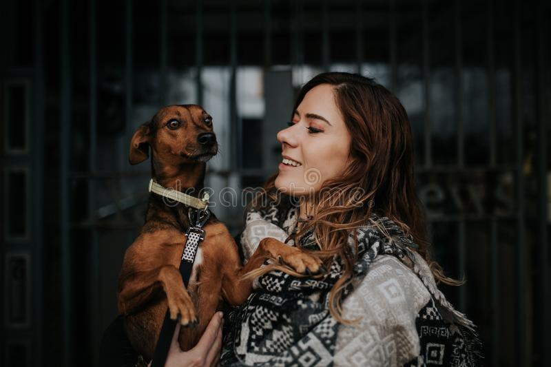Beautiful woman holding her dog with a smile. royalty free stock image