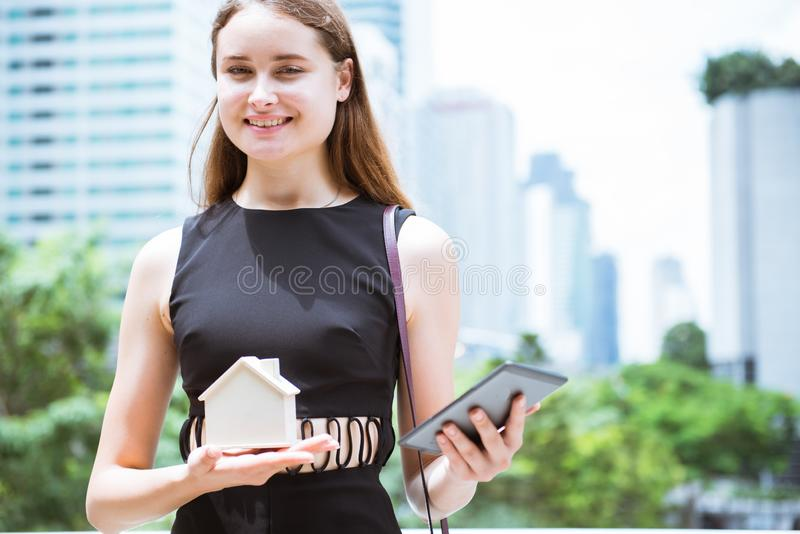 Young woman holding house model in her hand stock photos