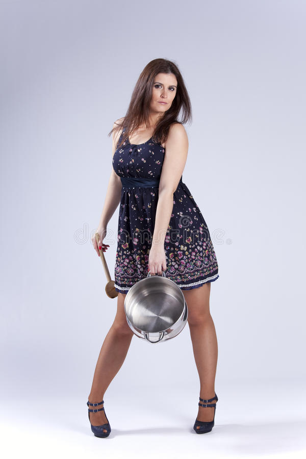 Beautiful woman holding a kitchen utensil. Fashion beautiful woman holding a kitchen pan and a wood spoon royalty free stock image