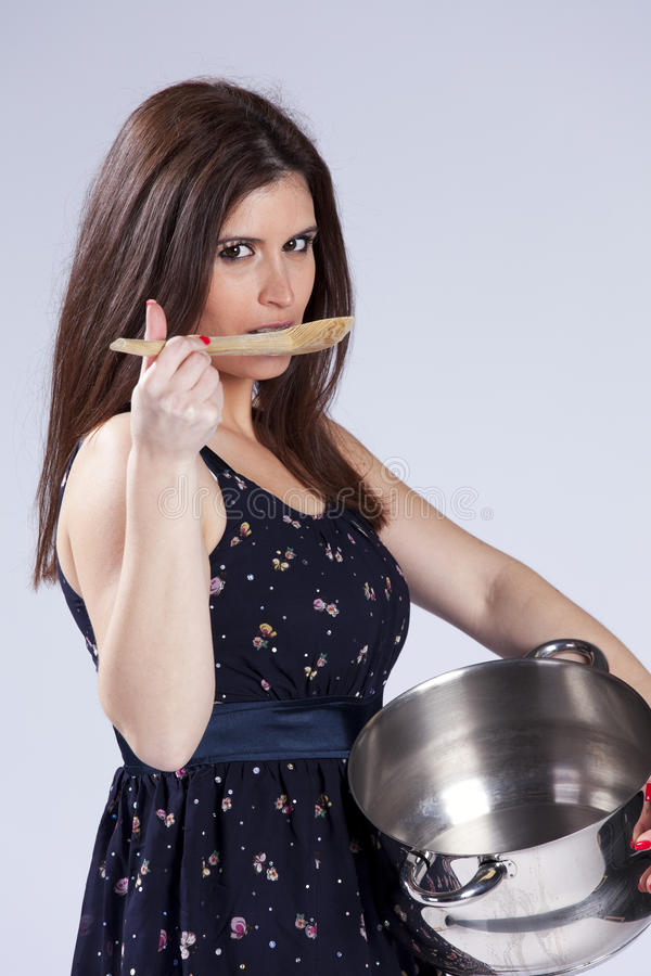 Beautiful woman holding a kitchen utensil. Fashion beautiful woman holding a kitchen pan and a wood spoon stock photography