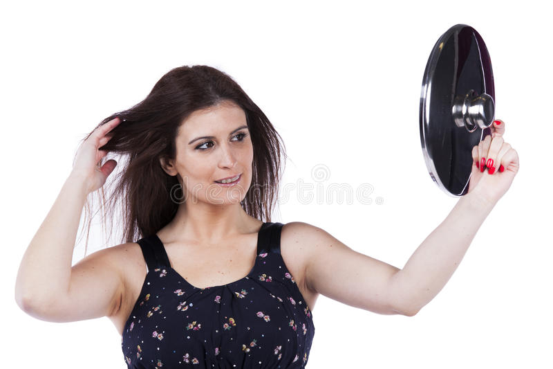 Beautiful woman holding a kitchen utensil. Fashion beautiful woman looking to the mirror on a kitchen pan stock image
