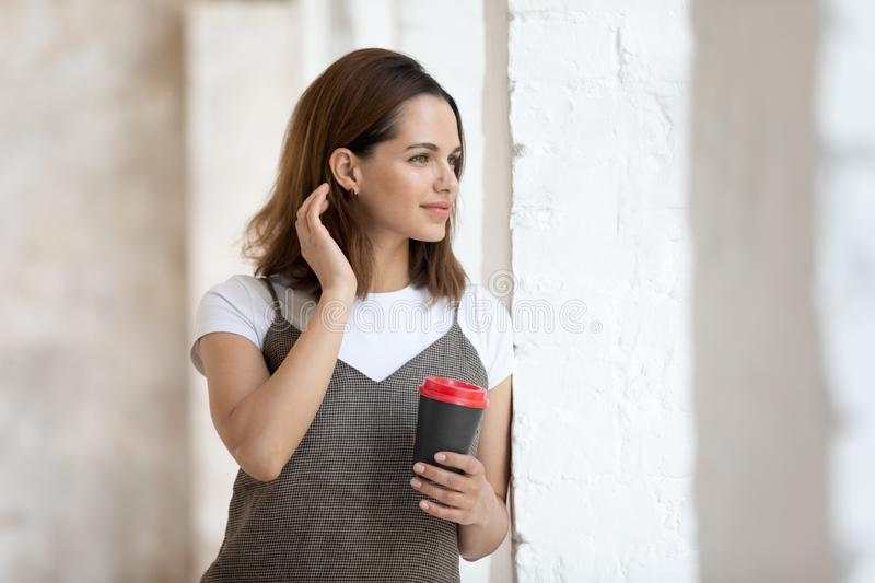 Beautiful woman holding paper coffee cup looking out the window royalty free stock photography