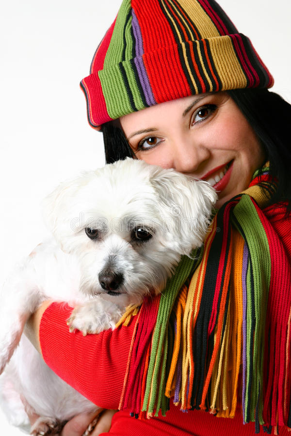 Beautiful woman holding a pet dog. A beautiful smiling vibrant woman affectionately cuddling a pet white maltese terrier dog stock photos