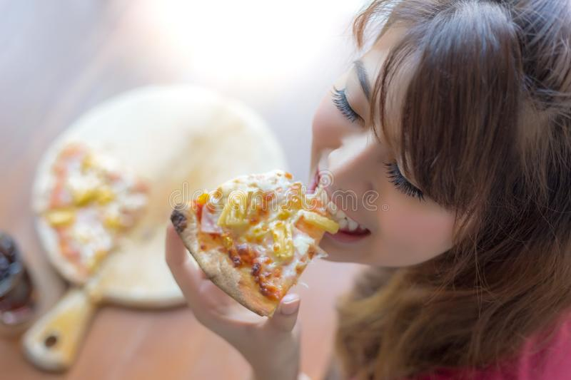 A beautiful woman is holding a piece of pizza and eating it. Pretty asian girl feels happy and enjoy eating the pizza. It looks so royalty free stock image