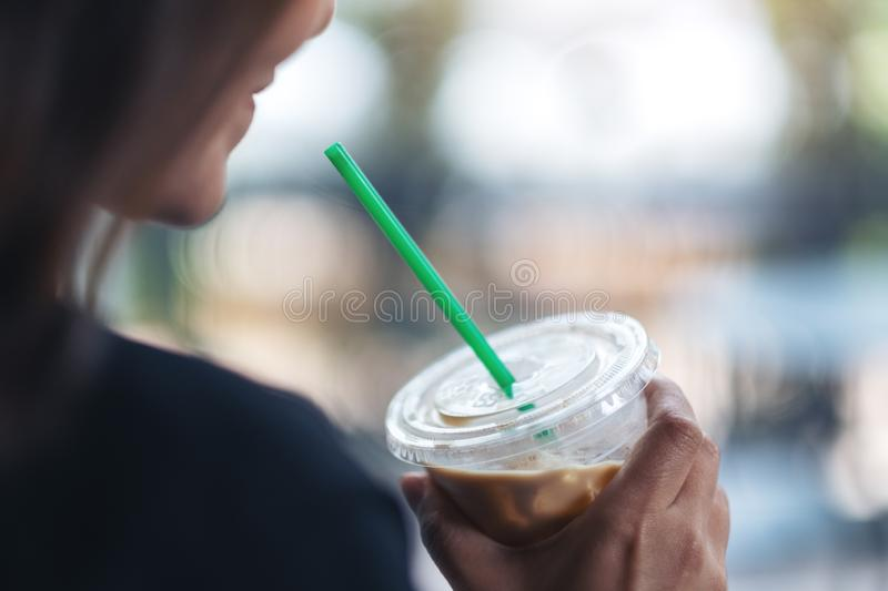 A beautiful woman holding a plastic glass of iced coffee royalty free stock photos