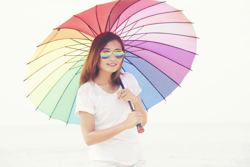 Beautiful woman holding rainbow colorful umbrella. Travel Concept stock photo