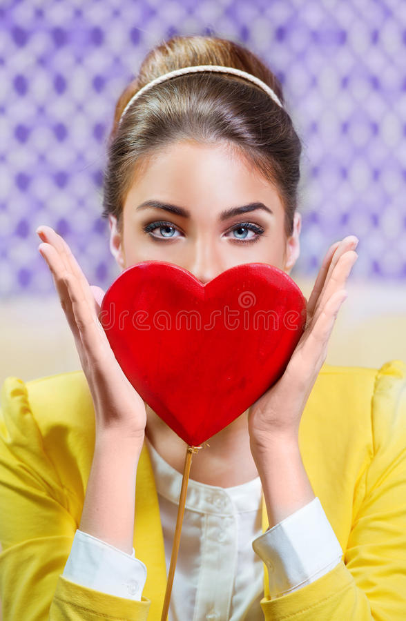 Beautiful woman holding a red heart royalty free stock image