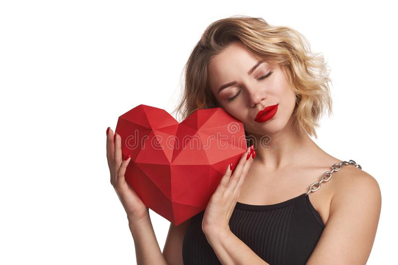 Beautiful woman holding red polygonal paper heart shape enjoying with closed eyes stock photos