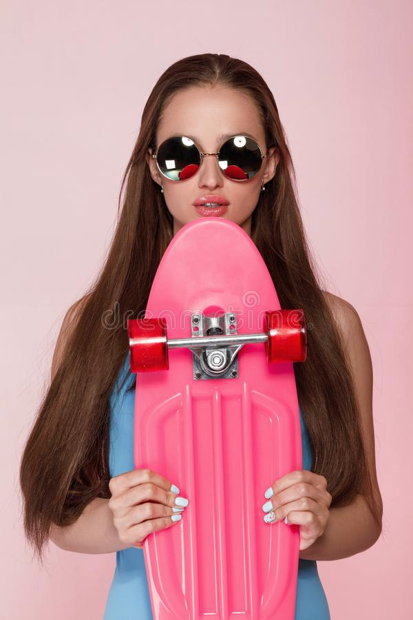 Beautiful woman holding skateboard royalty free stock photo