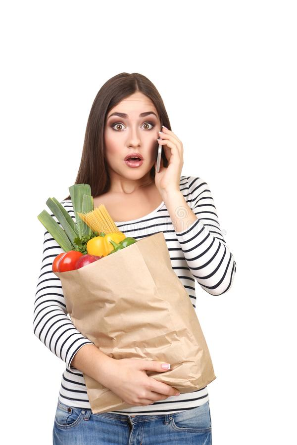 Woman holding smartphone and grocery shopping bag royalty free stock image