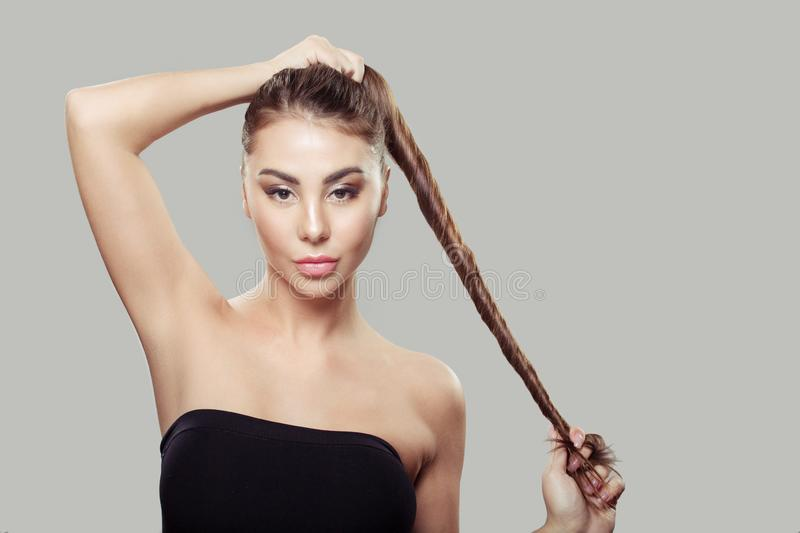 Beautiful woman holding straight shiny strong hair. Gray background royalty free stock images