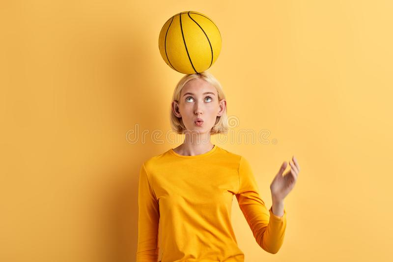 Beautiful woman holds basket ball on head isolated on yellow background stock images
