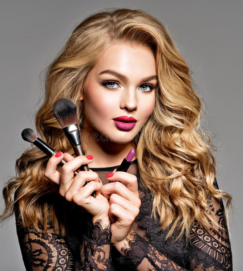 Beautiful woman holds cosmetic tools. Makeup royalty free stock image