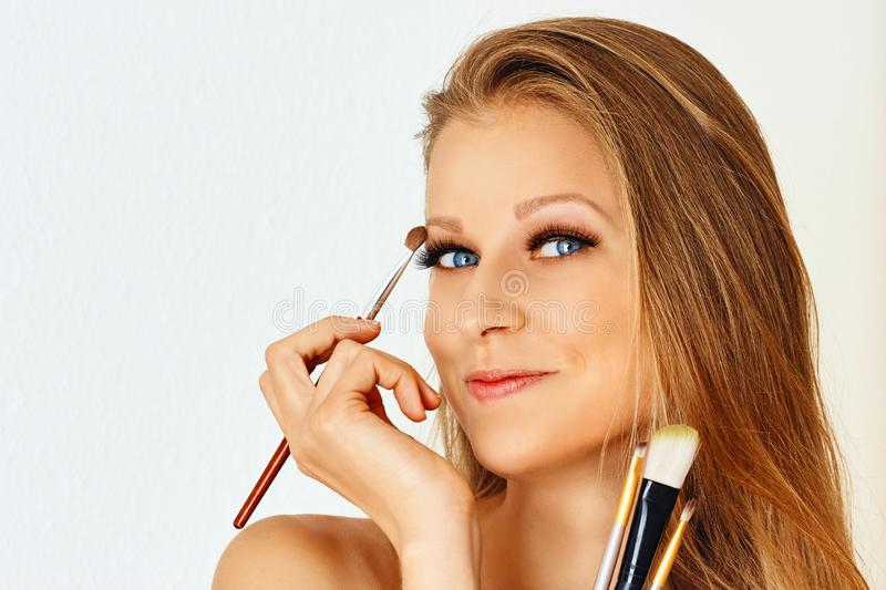 Beautiful woman holds make-up brush and puts on cosmetics on her face. Make up, cosmetics, beauty, eye lash extension stock photography