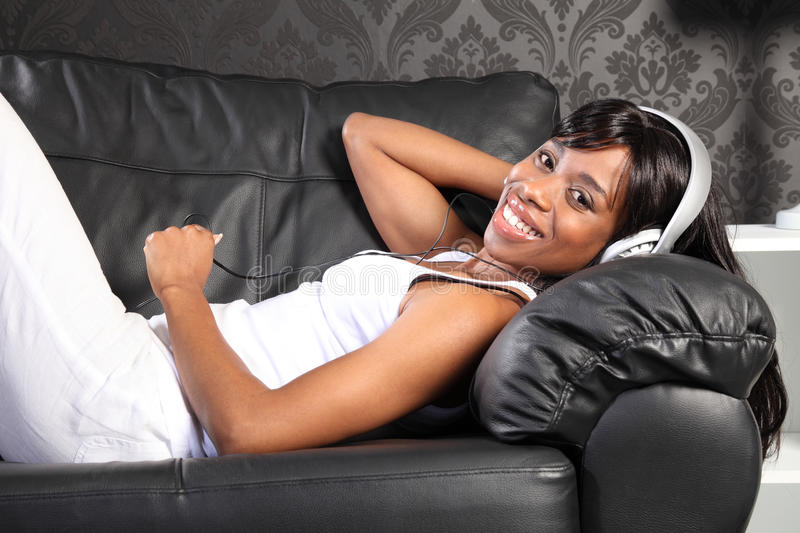 Beautiful woman at home lying down enjoying music. Beautiful smiling young african american woman lying on black leather sofa at home, headphones on listening to stock photography