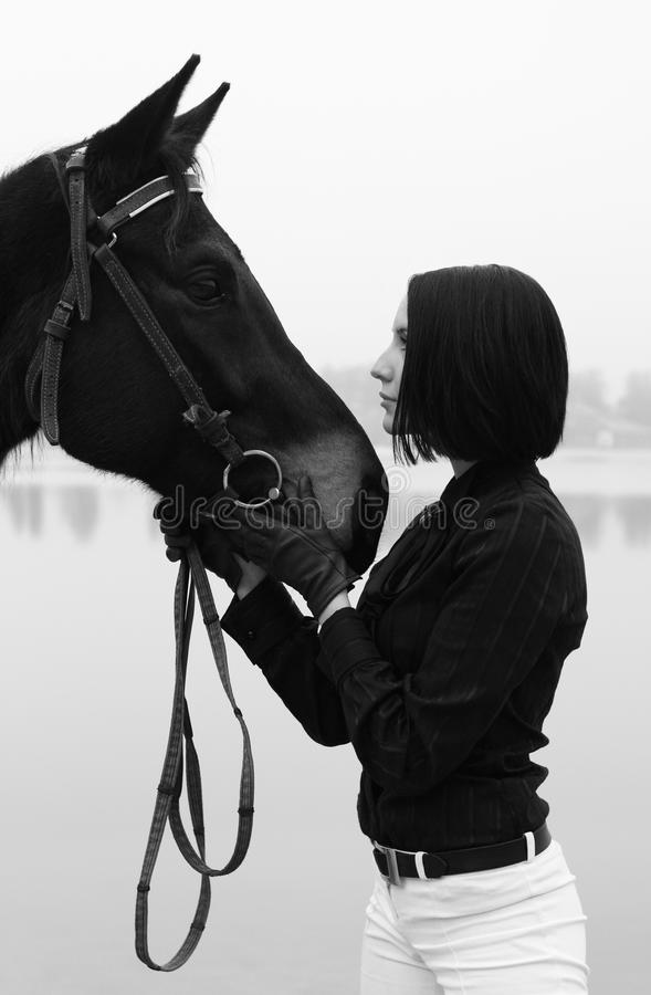 Beautiful woman with horse in black and white. Beautiful elegant woman with horse in black and white royalty free stock photo