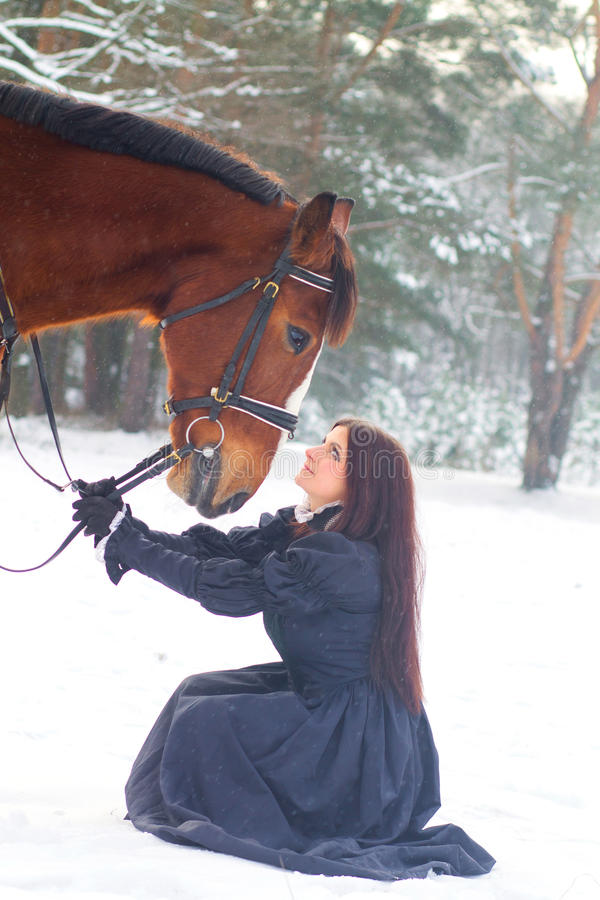 Beautiful woman and horse in winter stock photo