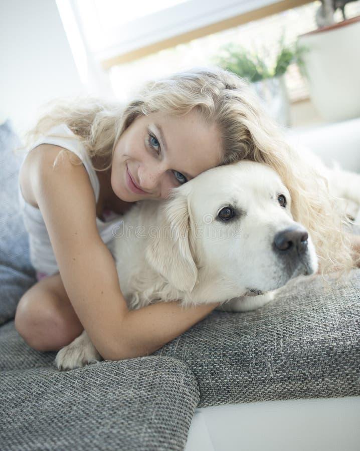 Beautiful woman hugging dog on sofa stock image