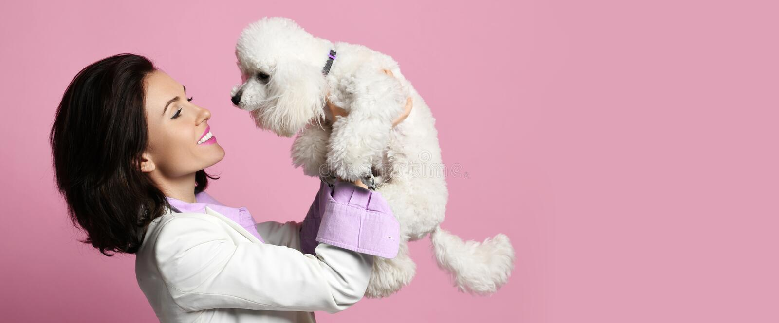 Beautiful woman hugging her lovely white poodle dog puppy on pink happy smiling royalty free stock photography
