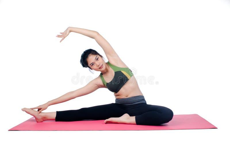 Beautiful woman indoor exercising using pink yoga mat. Photo of Beautiful woman indoor exercising using pink yoga mat stock photography