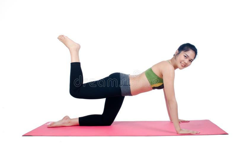 Beautiful woman indoor exercising using pink yoga mat. Photo of Beautiful woman indoor exercising using pink yoga mat royalty free stock photos