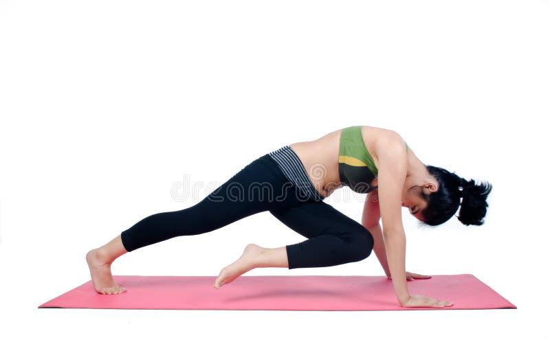 Beautiful woman indoor exercising using pink yoga mat. Photo of Beautiful woman indoor exercising using pink yoga mat stock image