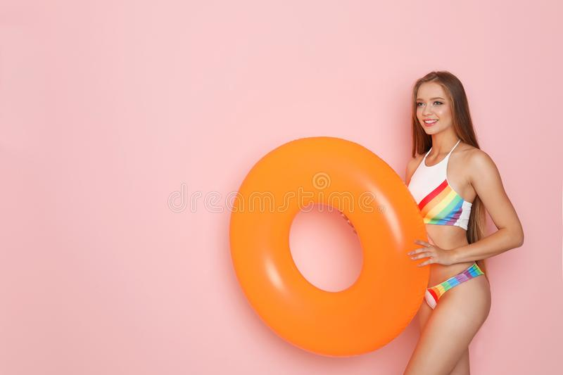 Beautiful woman with inflatable ring wearing bikin. I on color background stock images