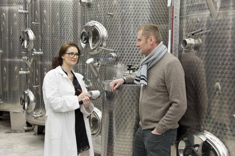 Beautiful woman inspector talking with manager in winery. royalty free stock photos