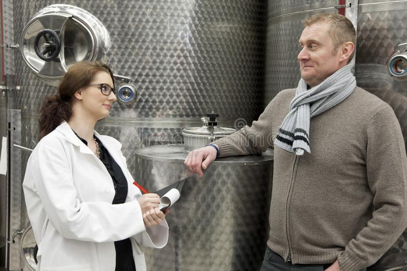 Beautiful woman inspector talking with manager in winery. royalty free stock images
