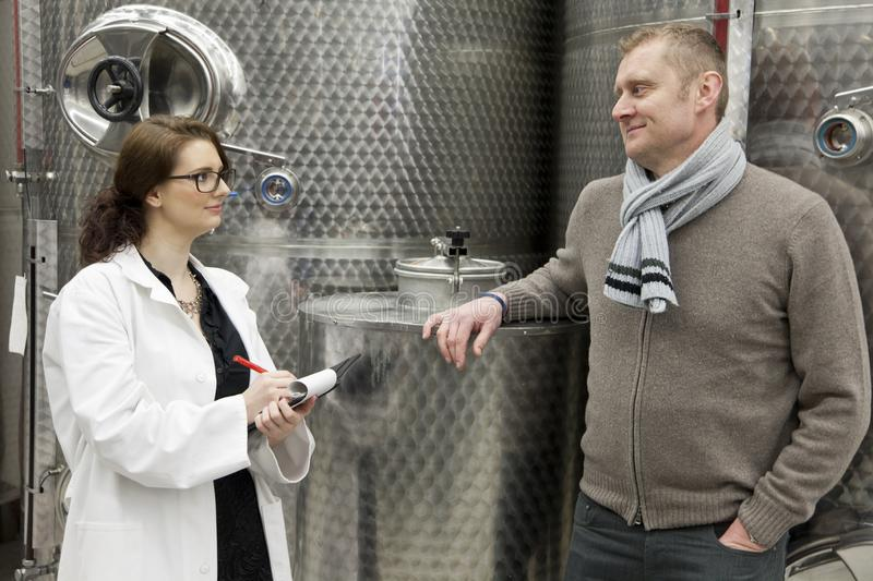Beautiful woman inspector talking with manager in winery. stock image
