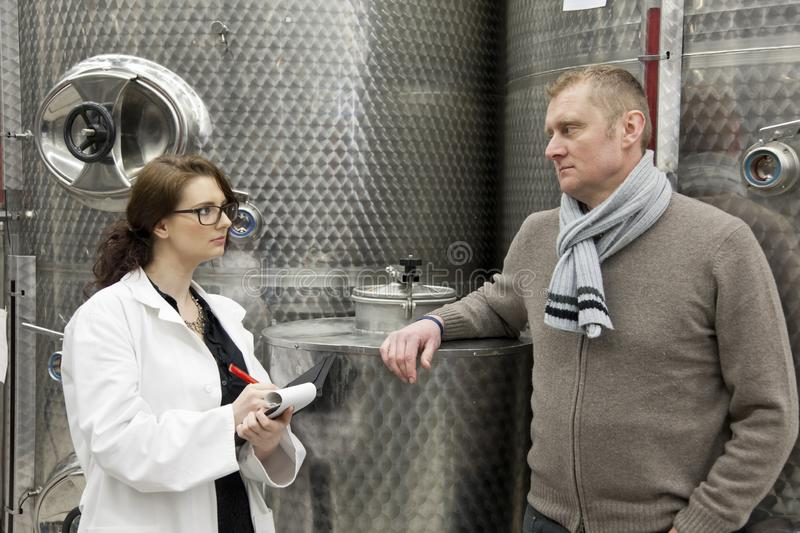 Beautiful woman inspector talking with manager in winery. stock photo