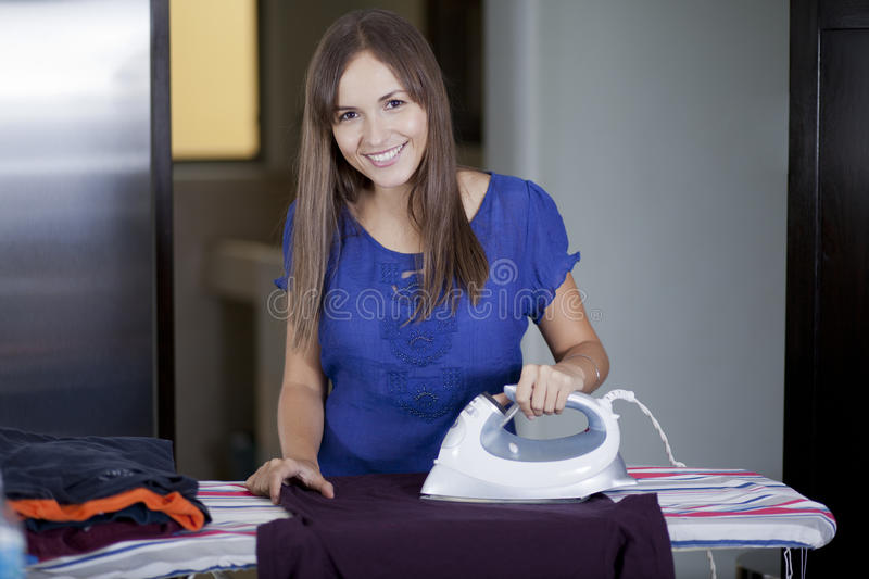 Beautiful woman ironing some clothes. Cute young housewife ironing some clothes and smiling royalty free stock photo