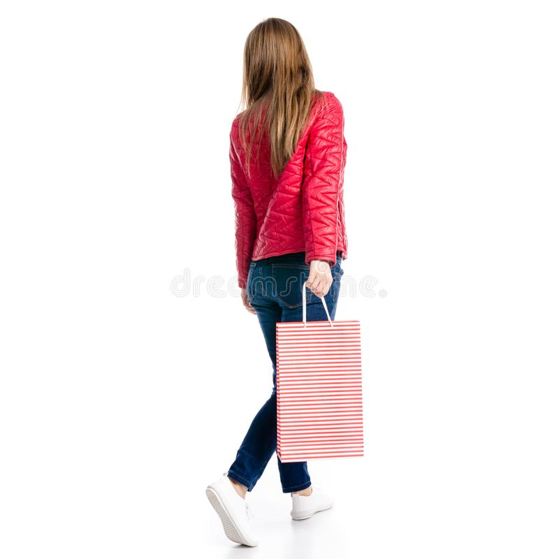 Beautiful woman in jacket and jeans in hand bag package goes. On white background isolation, back view stock image