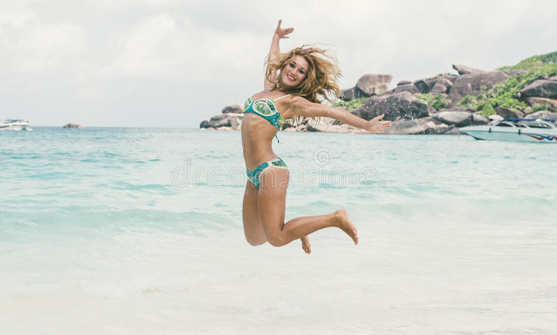 Beautiful woman jumping on white sand royalty free stock images
