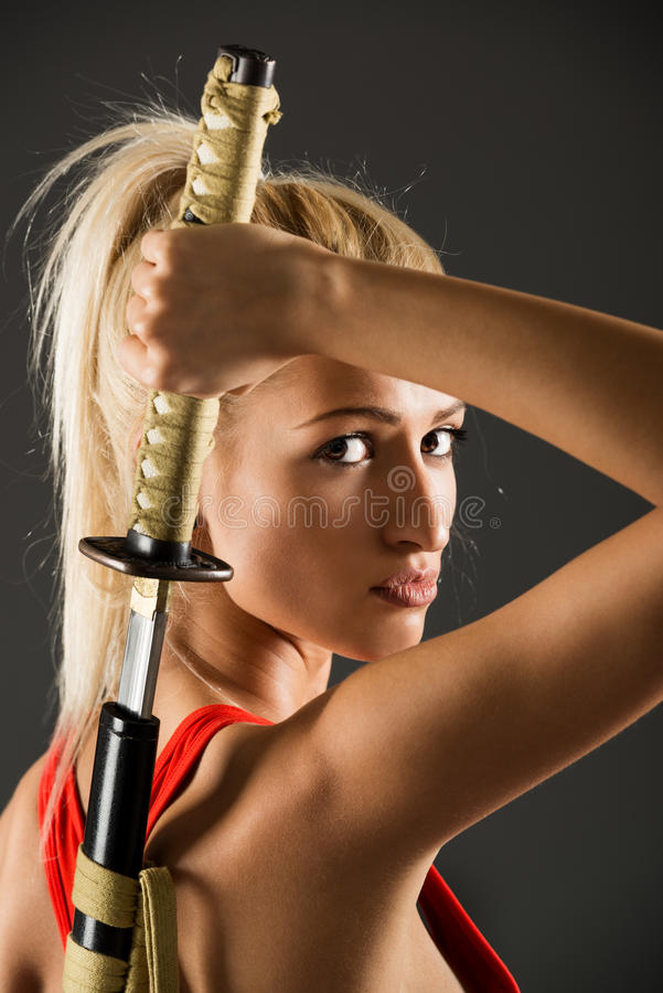 Beautiful Woman With Katana. Profile of beautiful young blond woman who draws a katana behind back and with a serious expression on her face looking at the royalty free stock photography