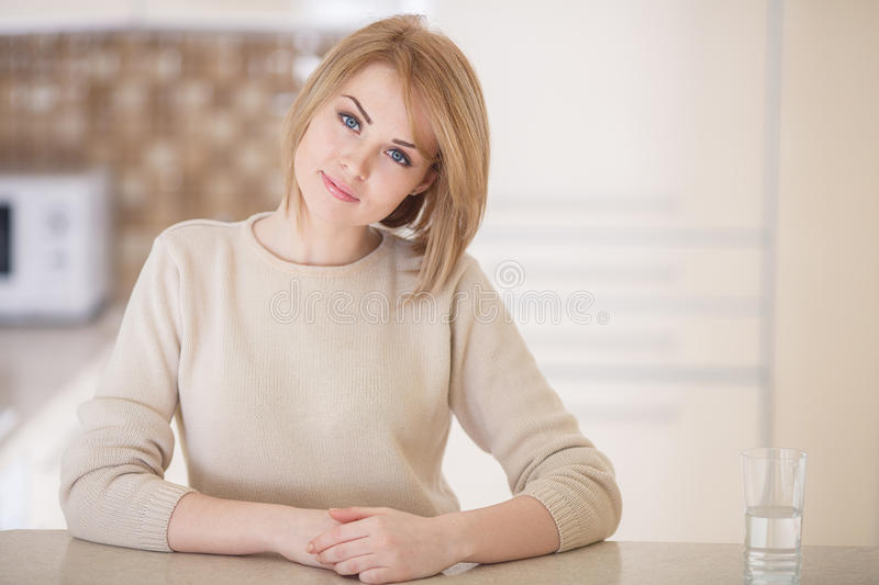 Beautiful woman in the kitchen with a glass of water royalty free stock photo