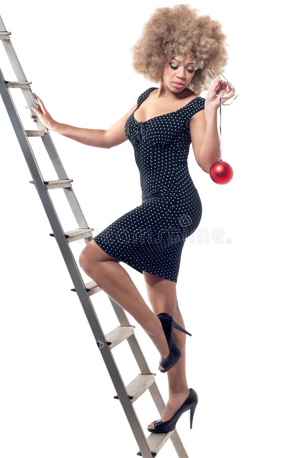 Beautiful woman on ladder holding a Christmas ball stock photo