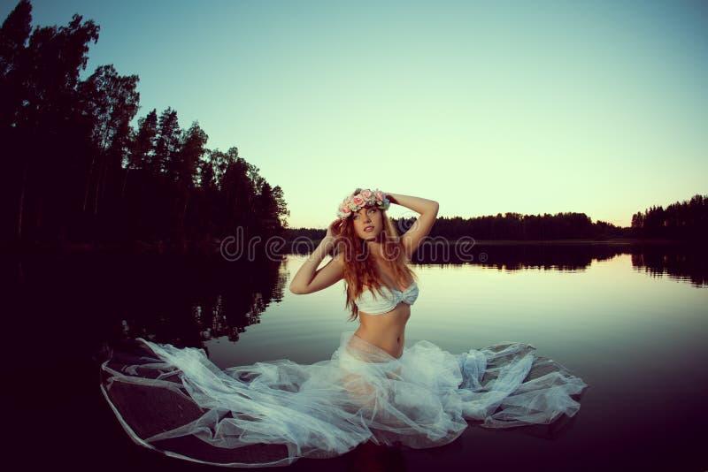 Beautiful woman in a lake at night. Girl at sunset in the lake. Beautiful woman in a lake at night. Beauty girl at sunset in the lake stock image