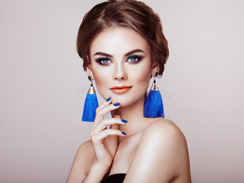 Beautiful Woman with Large Earrings Tassels. Jewelry Blue color. Perfect Makeup and Elegant Hairstyle. Blue Make-up Arrows royalty free stock photography