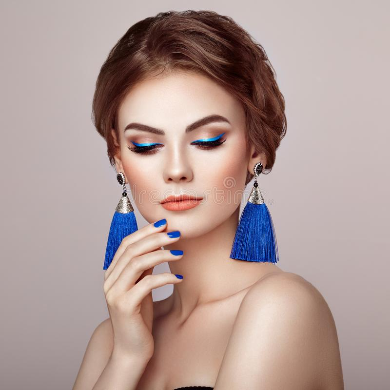 Beautiful Woman with Large Earrings Tassels. Jewelry Blue color. Perfect Makeup and Elegant Hairstyle. Blue Make-up Arrows. Blue nails manicure royalty free stock photography
