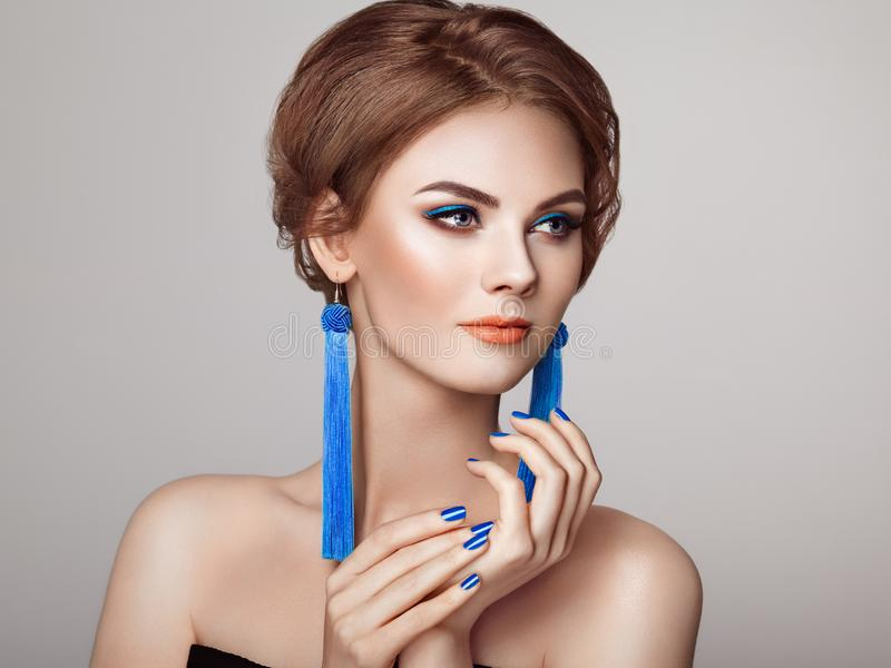 Beautiful Woman with Large Earrings Tassels. Jewelry Blue color. Perfect Makeup and Elegant Hairstyle. Blue Make-up Arrows. Blue nails manicure royalty free stock photos