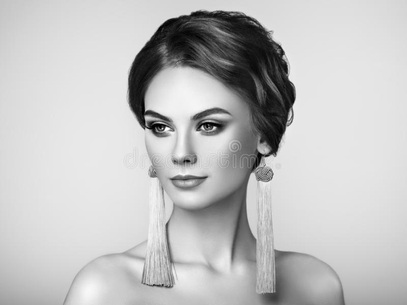 Beautiful Woman with Large Earrings Tassels. Jewelry. Perfect Makeup and Elegant Hairstyle. Fashion Make-up Arrows. Black and White Photo royalty free stock photo
