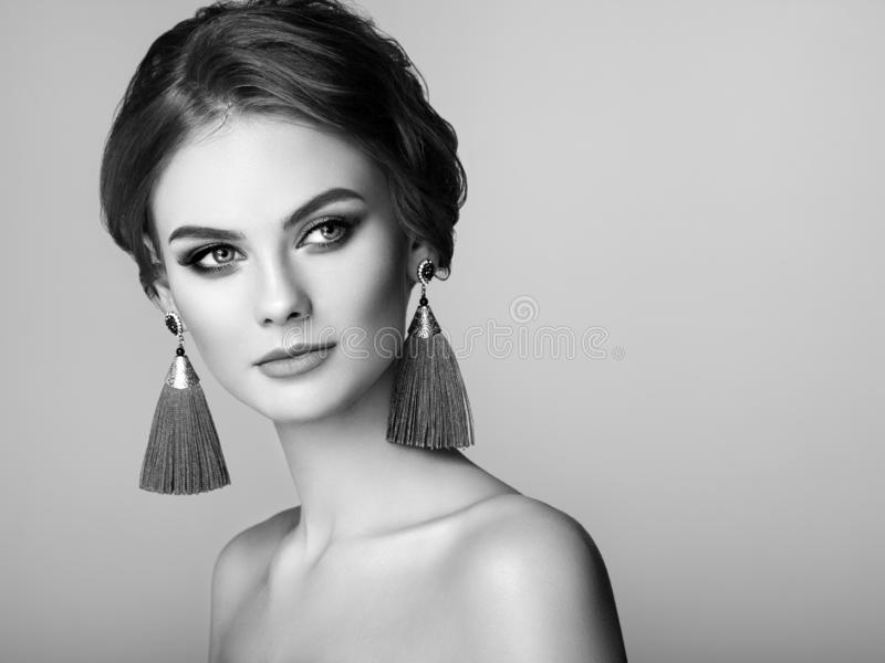 Beautiful Woman with Large Earrings Tassels. Jewelry. Perfect Makeup and Elegant Hairstyle. Fashion Make-up Arrows. Black and White Photo stock images