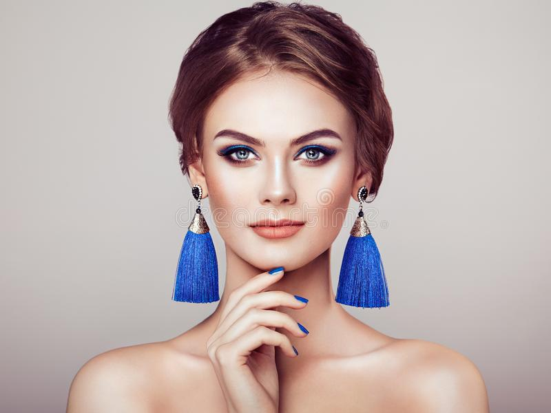 Beautiful Woman with Large Earrings Tassels. Jewelry Blue color. Perfect Makeup and Elegant Hairstyle. Blue Make-up Arrows royalty free stock photo