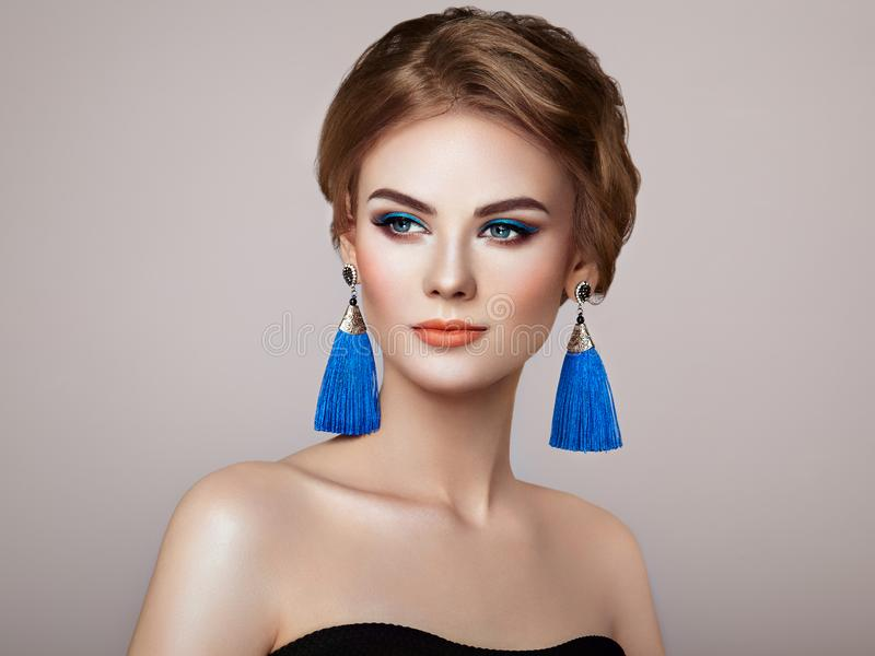 Beautiful Woman with Large Earrings Tassels. Jewelry Blue color. Perfect Makeup and Elegant Hairstyle. Blue Make-up Arrows royalty free stock photos