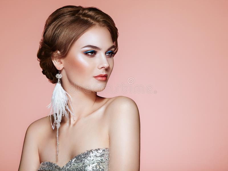 Beautiful Woman with Large Earrings Tassels. Jewelry White Color. Perfect Makeup and Elegant Hairstyle. Blue Make-up Arrows royalty free stock photography