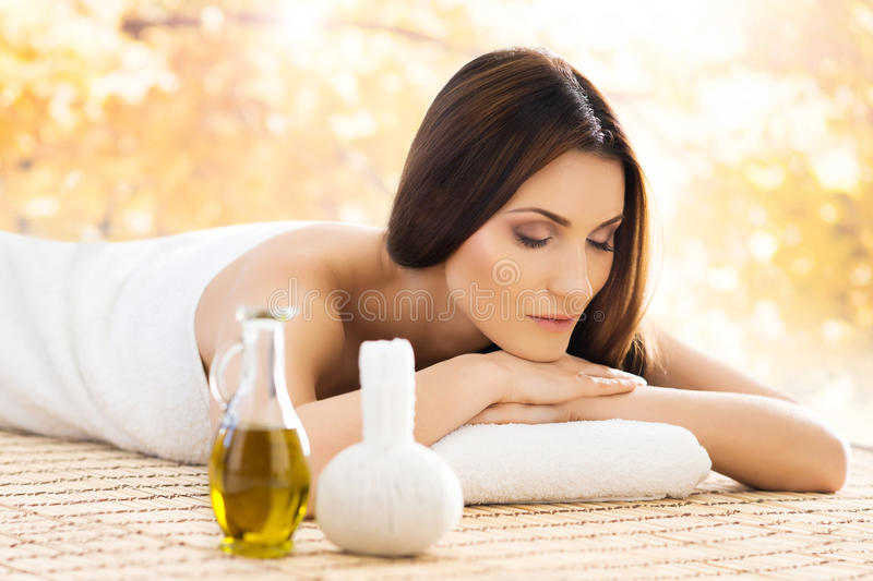 Beautiful woman laying on a mat having a smell of aroma in original spa salon. stock photos