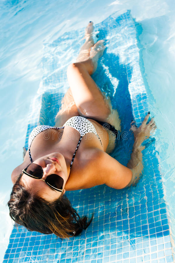 Beautiful woman laying in the pool with pure water royalty free stock image