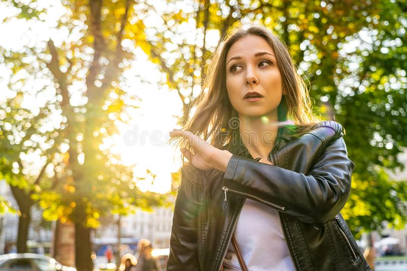 Beautiful woman in leather jacket on the street with sun backlight. Portrait photography with female model outdoor stock photography